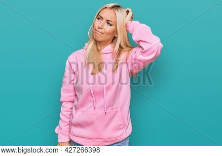 Young blonde woman wearing casual sweatshirt confuse and wondering about question. uncertain with doubt, thinking with hand on head. pensive concept.