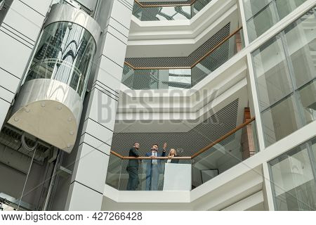 Business people standing at the balcony of modern office building and talking to each other during a meeting