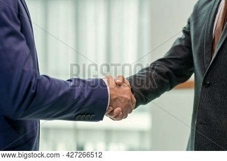 Close-up of business partners shaking hands to each other before meeting at office