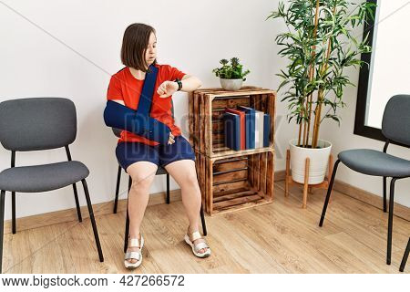 Young down syndrome woman sitting at doctor waiting room with arm injury checking the time on wrist watch, relaxed and confident