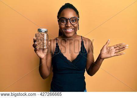 African american woman with braided hair holding lentils celebrating achievement with happy smile and winner expression with raised hand