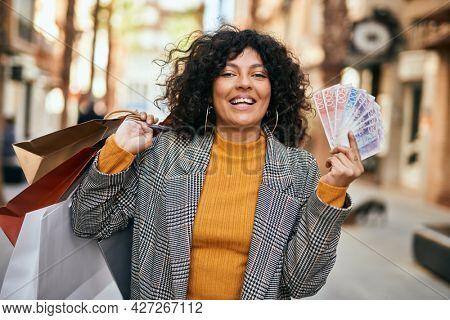 Young hispanic woman shopping holding swedish krone banknotes at the city.