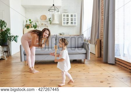 Mommy Sings A Song Using A Kitchen Spatula Like Microphone With Little Cute Daughter In Cozy Light L