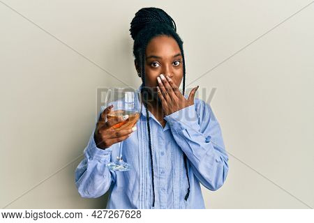 African american woman with braided hair drinking a glass of white wine covering mouth with hand, shocked and afraid for mistake. surprised expression