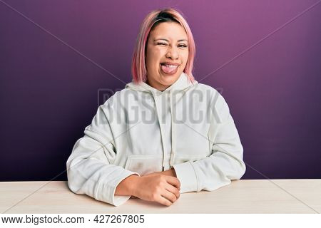 Hispanic woman with pink hair wearing casual sweatshirt sitting on the table winking looking at the camera with sexy expression, cheerful and happy face.