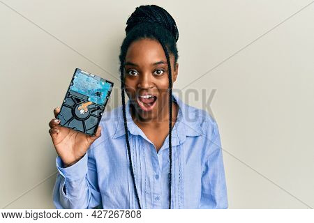 African american woman with braided hair holding hard disk scared and amazed with open mouth for surprise, disbelief face