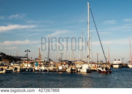 Loutra, Kythnos, Greece, 03/06/2019. Row Of Sailing And Fishing Boats Moored At The Pier In Loutra M