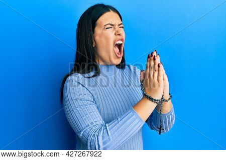 Beautiful brunette woman praying holding catholic rosary angry and mad screaming frustrated and furious, shouting with anger. rage and aggressive concept.