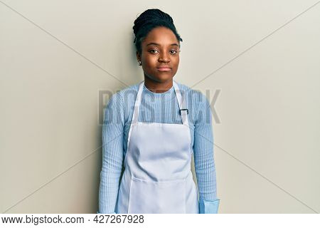 African american woman with braided hair wearing cleaner apron and gloves relaxed with serious expression on face. simple and natural looking at the camera.