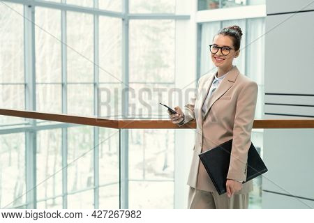 Portrait of young elegant businesswoman in suit smiling at camera while standing at office corridor with folder and using her mobile phone