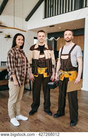 Female client and two repairmen in workwear standing in front of camera