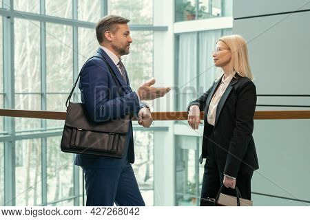 Businessman with briefcase talking to his colleague while they standing at office corridor