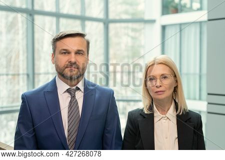 Portrait of mature business couple in formalwear looking at camera while standing at office corridor