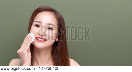 Beautiful Young Woman With Silky Skin Using Cotton Pads On Green Background