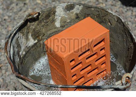 Wetting Of Bricks, Soaking Bricks In Water Before Laying The Bricks For Good Mortar Strength.