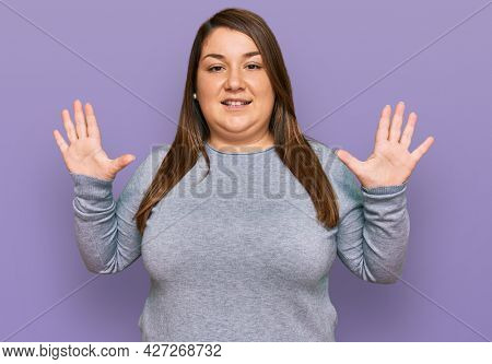 Beautiful brunette plus size woman wearing casual clothes showing and pointing up with fingers number ten while smiling confident and happy.