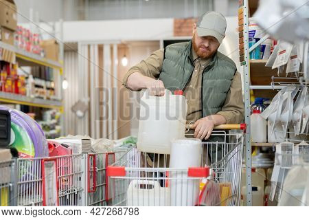 Bearded customer putting household goods into shopping cart in hardware store