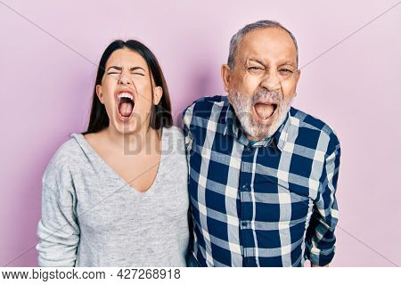 Hispanic father and daughter wearing casual clothes angry and mad screaming frustrated and furious, shouting with anger. rage and aggressive concept.