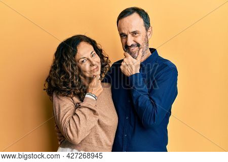 Middle age hispanic couple wearing casual clothes looking confident at the camera smiling with crossed arms and hand raised on chin. thinking positive.