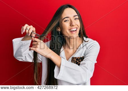 Young hispanic girl cutting hair using scissors smiling and laughing hard out loud because funny crazy joke.