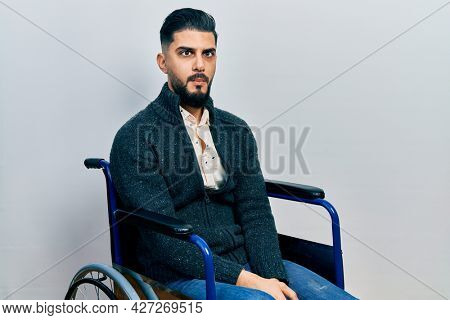 Handsome man with beard sitting on wheelchair making fish face with lips, crazy and comical gesture. funny expression.