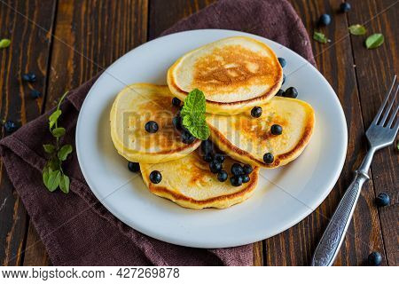Pancakes With Corn Flour And Blueberries On A White Plate On A Brown Wooden Background. Pancake Reci