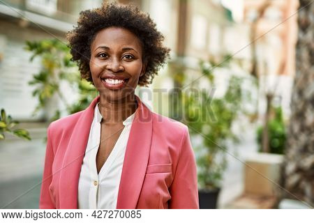 Beautiful business african american woman with afro hair smiling happy and confident outdoors at the city