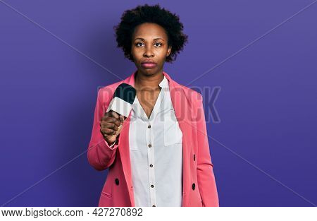 African american woman with afro hair holding reporter microphone thinking attitude and sober expression looking self confident