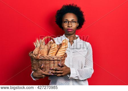 Young african american woman holding wicker basket with bread thinking attitude and sober expression looking self confident