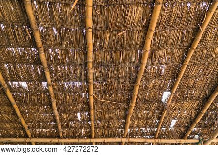 Old Dry Grass Roof With Bamboo Beam Structure. Tropical Texture Background