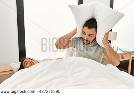 Man covering ears with pillow irritated for snore lying in bed at home.