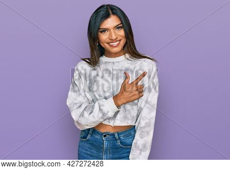 Young latin transsexual transgender woman wearing casual clothes cheerful with a smile of face pointing with hand and finger up to the side with happy and natural expression on face