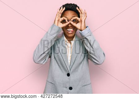 Young african american woman wearing business clothes doing ok gesture like binoculars sticking tongue out, eyes looking through fingers. crazy expression.
