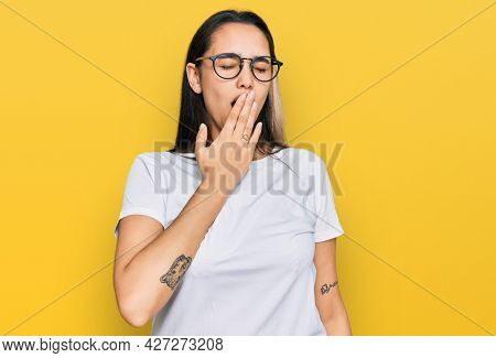 Young hispanic woman wearing casual white t shirt bored yawning tired covering mouth with hand. restless and sleepiness.