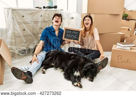 Young caucasian couple with dog holding our first home blackboard at new house angry and mad screaming frustrated and furious, shouting with anger. rage and aggressive concept.