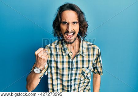 Young hispanic man wearing casual clothes angry and mad raising fist frustrated and furious while shouting with anger. rage and aggressive concept.