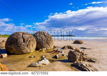 The concept of exotic and ecological tourism. The huge round stone boulders Moeraki and their remains on sandy beach. The popular tourist attraction. New Zealand. Low tide in the Pacific ocean