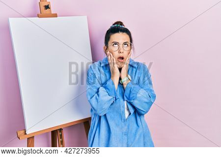 Young hispanic woman standing by painter easel stand tired hands covering face, depression and sadness, upset and irritated for problem