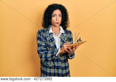 Young latin girl wearing business clothes writing on clipboard depressed and worry for distress, crying angry and afraid. sad expression.