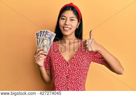 Young woman holding 5000 japanese yen banknotes smiling happy and positive, thumb up doing excellent and approval sign