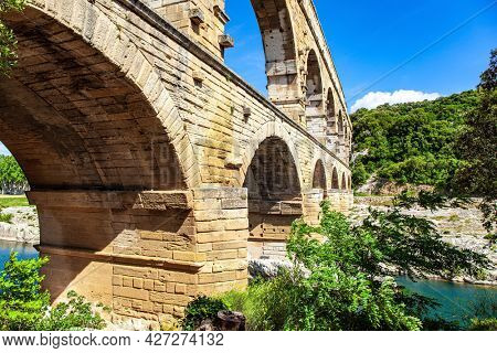 Picturesque antique bridge - aqueduct. The Pont du Gard is the tallest Roman aqueduct. Interesting trip to France. The shallow Gardon River. Bright sunny day