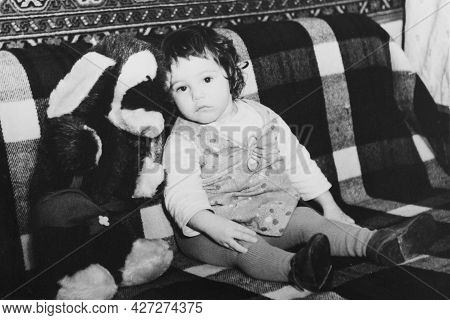 Vintage Photo Of Little Girl With A Toy Dog. Early 1980s. Old Surface, Soft Focus. Transferred Prope