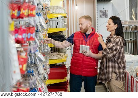 Sales manager showing new goods to young female consumer in household department