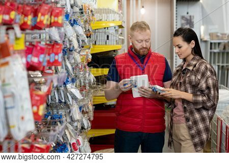 Young woman consulting with manager while buying household goods