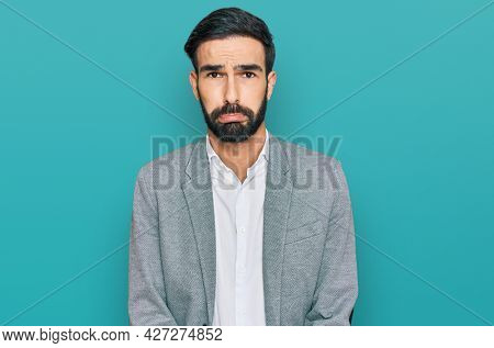 Young hispanic man wearing business clothes depressed and worry for distress, crying angry and afraid. sad expression.