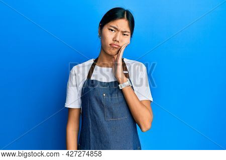 Young chinese woman wearing waiter apron touching mouth with hand with painful expression because of toothache or dental illness on teeth. dentist
