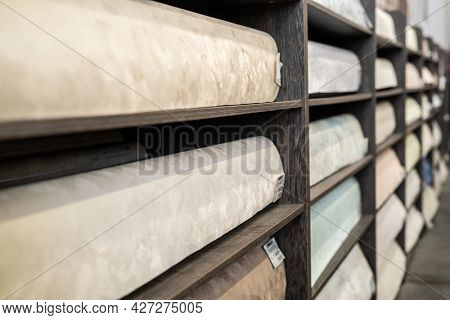 Shelves with rolled wallpapers in large hardware store