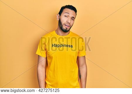 Hispanic man with beard wearing t shirt with happiness word message looking sleepy and tired, exhausted for fatigue and hangover, lazy eyes in the morning.