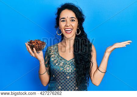 Young woman wearing bindi and traditional kurta dress holding bowl of star anise celebrating victory with happy smile and winner expression with raised hands