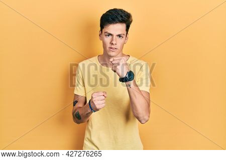Young hispanic man wearing casual yellow t shirt ready to fight with fist defense gesture, angry and upset face, afraid of problem